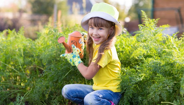 Little girl posing with watering can